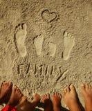 Familjfotspår i sanden på stranden Arkivbilder