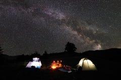 Familjfotvandrare som har en vila på natten som campar i berg arkivbilder