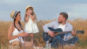 Familjgyckel i natur, den unga gladlynta pappan spelar gitarren, när hans härliga fru och lilla daugther applåderar händer lyckli lager videofilmer
