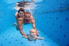 Familjgyckel i simbassäng - modern, fader, behandla som ett barn den undervattens- dyken Royaltyfri Foto