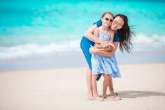 Familjgyckel på den vita sandiga stranden Modern och den lilla ungen tycker om sommarsemester Royaltyfria Bilder