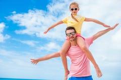 Familjgyckel på vit sand Le fadern och det förtjusande barnet som spelar på den sandiga stranden på en solig dag Fotografering för Bildbyråer