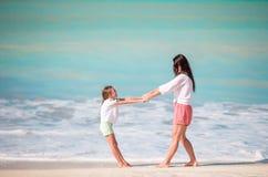 Familjgyckel på vit sand Le modern och det förtjusande barnet som spelar på den sandiga stranden på en solig dag Arkivbilder