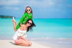 Familjgyckel på vit sand Le modern och det förtjusande barnet som spelar på den sandiga stranden på en solig dag Royaltyfri Bild