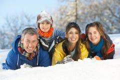 familjgyckel som har snöig barn för liggande Arkivbild
