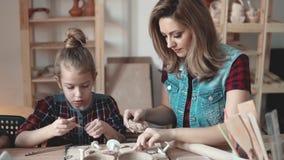 Familjhobby modern och barnet är förlovade, i att modellera för lera stock video