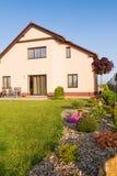 Familjhuset med en gräsmatta och våren arbeta i trädgården Arkivfoton