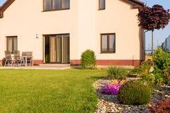Familjhuset med en gräsmatta och våren arbeta i trädgården Arkivfoto