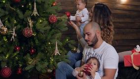 Familjjul atmosfär, barn med leksaker på handföräldrar dekorerar tillsammans av träd i xmas-helgdagsafton lager videofilmer