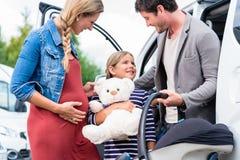 Familjköpandebil, moder, fader och barn på återförsäljaren Arkivfoton
