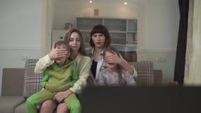 FamiljklockaTV Äldre systrar stänger deras ögon till barn på grund av dåligt olämpligt innehåll på skärmen inföding stock video