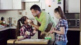 Familjkockar och lekar som pudrar varje andra med mjöl arkivfilmer
