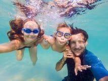Familjkondition - modern, fader, behandla som ett barn sonen lär att simma tillsammans, dyken som är undervattens- med gyckel i d royaltyfria bilder