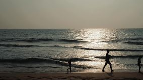 Familjkonturfader och barn som spelar på stranden på solnedgångtiden Begrepp av den vänliga lyckliga familjen arkivfilmer