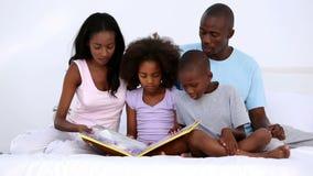 Familjläsebok på säng stock video
