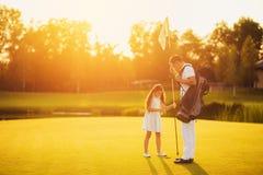 Familjlek av golf Fadern och dottern får tillsammans flaggan från hålet i golfbanan Royaltyfria Bilder