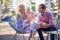 Familjlivsstilstående av en mum och en farsa med deras barn som sitter på utomhus- hopfällbar stol arkivfoto
