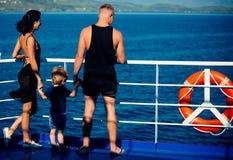 Familjlopp med ungen på moder- eller faderdag Moder och fader med sonblick på havet på stranden Sommarsemester av arkivfoton