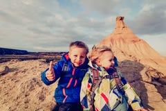 Familjlopp - pysen och flickan tycker om att fotvandra i berg arkivbilder
