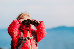 Familjloppliten flicka med kikare som undersöker naturen arkivfoto