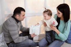 Familjmamma, farsa och dotter hemma på bakgrunden av julgarnering och gåvor arkivfoto