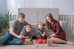 Familjmamman, farsan och två tvilling- bröder spelar byggande tillsammans ut ur träkvarter på golvet royaltyfri foto