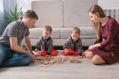 Familjmamman, farsan och två tvilling- bröder spelar byggande tillsammans ut ur träkvarter på golvet royaltyfri fotografi