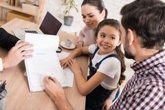 Familjmannen med frun och dottern undertecknar försäljningsavtalet i regeringsställning av fastighetsmäklaren arkivbild
