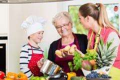 Familjmatlagning i multigenerational hushåll med sonen, moder, royaltyfri bild