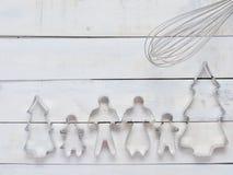 Familjmetallkakan eller kexskäraren som komponeras av fader, modern, brodern, syster och, sörjer trädet med metall viftar över gr Fotografering för Bildbyråer
