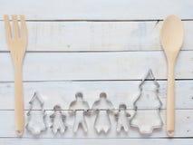 Familjmetallkakan eller kexskäraren som komponeras av fader, modern, brodern, syster och, sörjer trädet med träskeden och dela si Arkivfoto