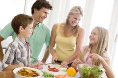 familjmålmealtime som tillsammans förbereder sig Arkivfoton