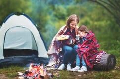 Familjmoder och barndotter som dricker te på en campa tur Arkivbild