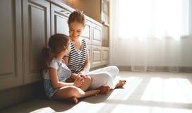 Familjmoder och barndotter som kramar i kök på golv arkivbilder