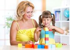 Familjmoder och dotter som spelar tegelstenar Fotografering för Bildbyråer