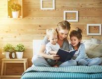 Familjmoder som läser till barnboken i säng Arkivbild