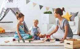 Familjmodern och barn spelar en leksakjärnväg i lekrum Royaltyfria Foton