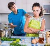 Familjpar med allvarliga framsidor som grälar i kök arkivfoto