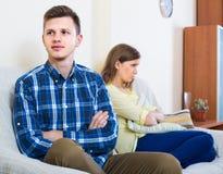 Familjpar med allvarliga framsidor som hemma grälar Arkivbild