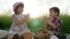 Familjpicknicknaturen på solnedgången, det roliga gulliga lilla barnet äter, ungen som lek i gräsplan parkerar picknicken i sollj lager videofilmer