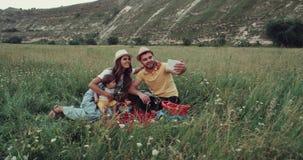 Familjpicknicktid i mitt av berget, genom att använda en minnestavla som talar med någon arkivfilmer