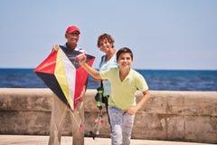 Familjpojke och morföräldrar som flyger draken nära havet Arkivbild