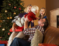 Familjöppningen presenterar framme av julgran Royaltyfri Fotografi