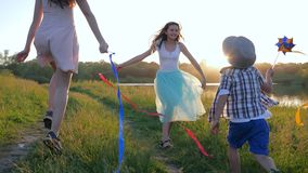 Familjrekreation, ljusa barn med kulöra band som kör längs grön äng längs floden i ljust solljus lager videofilmer