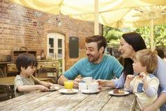 Familjsammanträde på den utomhus- kafétabellen som har lunch arkivbild