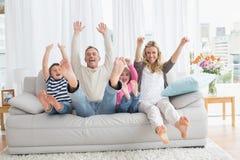 Familjsammanträde på en soffa och lyftaarmar royaltyfri foto