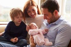 Familjsammanträde på Sofa With Newborn Baby Arkivbilder