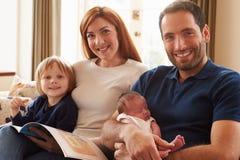 Familjsammanträde på Sofa With Newborn Baby Arkivbild