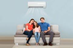 Familjsammanträde på Sofa Under Air Conditioning arkivbilder