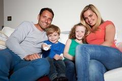 Familjsammanträde på Sofa Watching TV tillsammans royaltyfria bilder